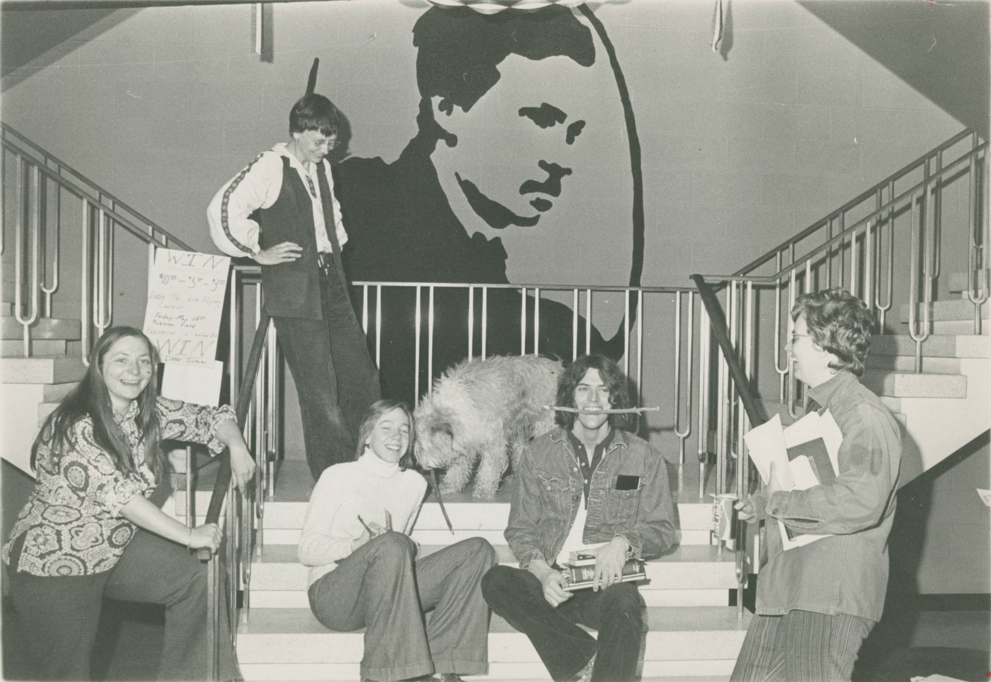 A black and white photo of students and faculty sitting and standing on the stairs in front of the William James mural in Lake Superior Hall.